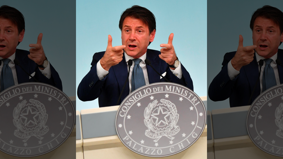 Italian Premier Giuseppe Conte gestures during a press conference in Rome, Monday, Sept. 24, 2018. Italy's populist government is making it harder for migrants to be approved for humanitarian protection. Interior Minister Matteo Salvini told reporters that the government at a Cabinet meeting Monday approved a decree setting tighter criteria for such protection, which accords a status less than full asylum. (Ettore Ferrari/ANSA via AP)