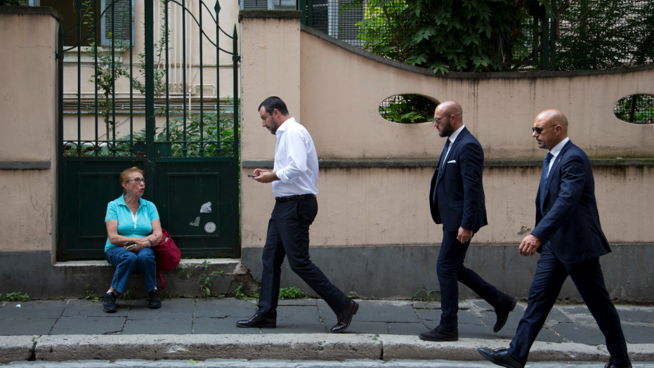 Interior Minister Matteo Salvini, second from left, is followed by security guards as he checks his phone while walking in downtown Rome after leaving Palazzo Chigi government office, Monday, Sept. 24, 2018. Salvini, who's cracking down on migrants, told reporters that the government at a Cabinet meeting Monday approved a decree setting tighter criteria for such protection, a status less than full asylum.  (AP Photo/Alessandra Tarantino)