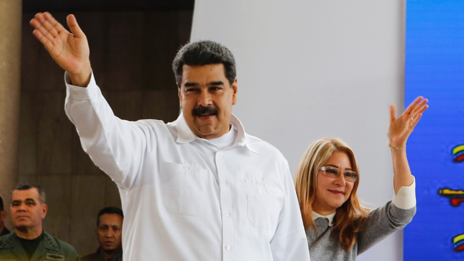 In this photo released by the Miraflores Press Office, Venezuela's President Nicolas Maduro, left, and his wife Cilia Flores greet supporters upon their arrival to a meeting with Colombian citizens that reside in Venezuela, In Caracas, Venezuela, Tuesday, Sept. 25, 2018. The Trump administration has slapped financial sanctions on four members of Venezuelan President Nicolas Maduro's inner circle, including his wife and the nation's vice president, on allegations of corruption. (Miraflores Press Office via AP)